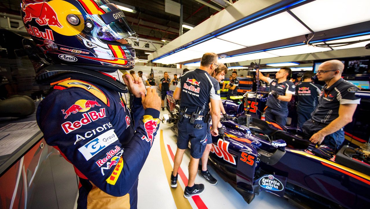 Carlos Sainz of Scuderia Toro Rosso looks on as the race engineers prepare his STR11 for a practice session at the Singapore Grand Prix on September 16, 2016