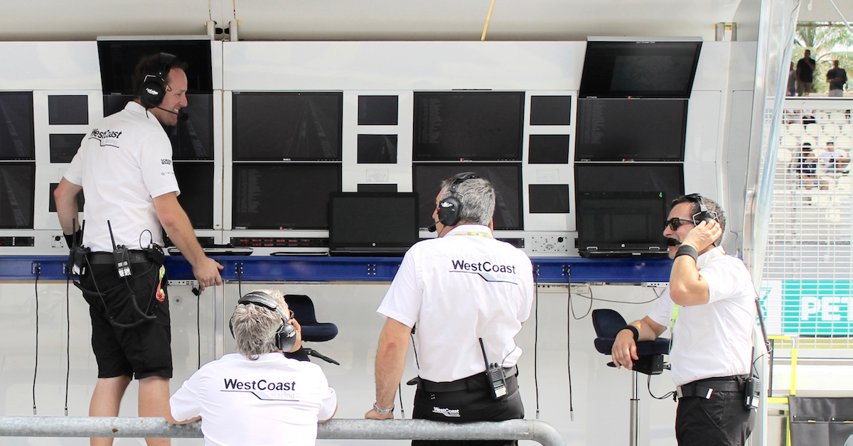 James Nixon, WestCoast Racing Team Manager (left) with other members of the team at a pit wall.